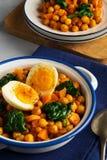 西班牙鸡豆和菠菜炖煮的食物用在浅灰色的背景的鸡蛋 背景烹调重点桔子肉菜饭红色米有选择性的西班牙酒 库存照片
