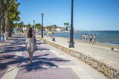 西班牙,穆尔西亚- 2019年6月22日:穿便服的愉快的年轻女人走在海滩 库存图片