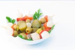 西班牙banderillas、串用腌制的橄榄,大蒜、腌汁、葱和红辣椒 免版税库存图片