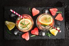 西瓜与西瓜片断的柠檬鸡尾酒在心脏形状的  华伦泰` s日概念 库存照片