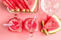 西瓜切片、冰块和圆滑的人在金属螺盖玻璃瓶在桃红色时尚背景顶视图 西瓜和smo创造性的布局  库存照片