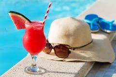 西瓜新鲜的汁圆滑的人饮料鸡尾酒拖鞋,帽子,太阳镜水池 免版税库存图片
