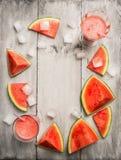 西瓜汁或圆滑的人与冰块和切的西瓜果子在土气木背景,顶视图 免版税库存图片