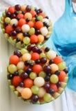 西瓜碗用西瓜填装了、甜瓜球、绿色和紫色葡萄和莓果 库存照片