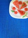 西瓜 作为在一块白色板材的星被形成的作为冰棍儿和西瓜片在蓝色五颜六色的背景 库存图片