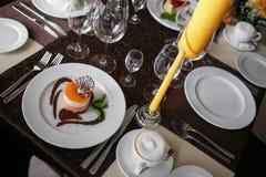 西番莲果蛋糕,在一块白色板材的奶油甜点点心有茶的 顶视图 库存图片