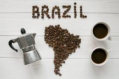 巴西的地图放置在与两个coffe杯子和咖啡壶的白色木织地不很细背景的由烤咖啡豆制成 库存照片