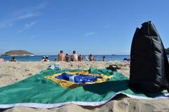 巴西的被伸出的旗子和在Barceloneta海滩沙子的一个黑背包在巴塞罗那,西班牙 免版税图库摄影