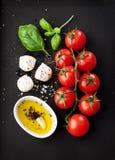 西红柿、无盐干酪乳酪、蓬蒿和橄榄油在黑黑板从上面 免版税库存图片