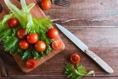 西红柿和沙拉叶子在切板有软的焦点的在背景 顶视图 复制文本空间 图库摄影