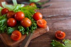 西红柿和沙拉叶子在切板有软的焦点的在背景 顶视图 复制文本空间 免版税库存照片