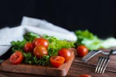 西红柿和沙拉叶子在切板有软的焦点的在背景 顶视图 复制文本空间 库存图片