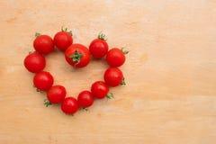 西红柿新鲜在木砧板,舱内甲板位置的心脏形状 免版税库存照片