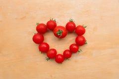 西红柿新鲜在木砧板,舱内甲板位置的心脏形状 免版税图库摄影