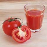 西红柿汁在木背景中 免版税库存图片