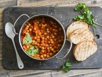 西红柿酱炖了在罐的鸡豆,并且烤了面包 在土气木背景的可口素食午餐 免版税图库摄影