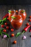西红柿酱调味汁用西红柿和炽热辣椒、大蒜和草本在一个玻璃瓶子在黑暗的背景 免版税库存图片
