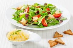 西红柿,油煎方型小面包片和毛鳞鱼獐鹿新鲜的沙拉,混杂的莴苣在白色盘离开在老木桌,顶视图 库存照片