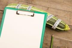 西葫芦、措施磁带和空白的剪贴板在棕色木桌上 图库摄影