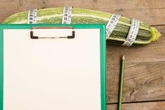 西葫芦、措施磁带和空白的剪贴板在棕色木桌上 免版税库存照片