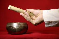 西藏唱歌碗和手在红色背景 免版税图库摄影