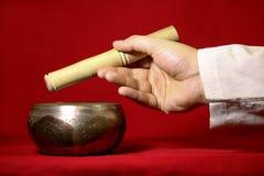 西藏唱歌碗和手在红色背景 免版税库存图片