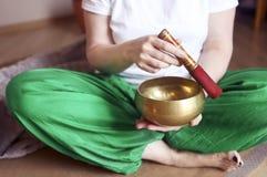 西藏唱歌碗在妇女的手上 图库摄影