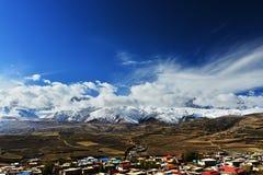 西藏在积雪覆盖的山前面的旗子飞行 免版税库存图片