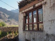 西藏房子在高山村庄,在房子的窗口里反射了领域,山,蓝天,夏天在Himal 免版税库存照片