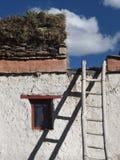 西藏房子:白色墙壁,一个小窗口,一架梯子,在一个屋顶平台为冬天放置草丛,西藏股票  库存图片