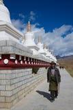 西藏老人在塔附近祈祷 免版税图库摄影