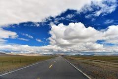 西藏长的路向前与在前面的高雪山 免版税库存照片