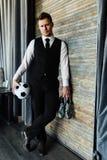 西装和足球的时髦的运动人 以顶楼墙壁为背景 免版税库存照片