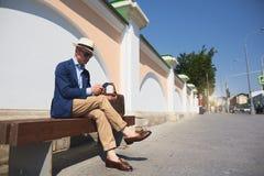 西装的一个人坐长凳和谈话在电话 免版税库存照片