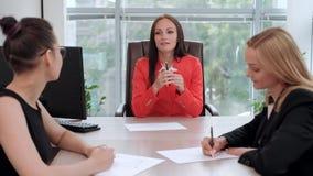 西装的三名年轻可爱的妇女坐在书桌并且谈论工作流 头和下级 影视素材