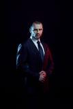西装的严肃的人,黑暗的背景,由后照蓝色和红色口气 免版税库存图片