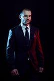 西装的严肃的人,黑暗的背景,由后照蓝色和红色口气 免版税图库摄影