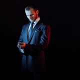 西装的严肃的人,黑暗的背景,由后照蓝色和红色口气 库存图片