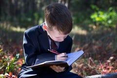 西装的小孩子采取在笔记本的笔记 免版税库存图片