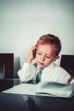 西装的小男孩谈话关于财政问题 库存图片