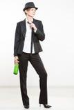 西装的端庄的妇女,拿着瓶酒精 免版税库存图片