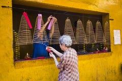 西贡,越南- 2015年2月18日-一个老妇人是灼烧的香火卷在罐子Hau寺庙的商店在胡志明市, 免版税图库摄影