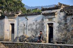 """西迪,安徽,中国†""""大约2017年10月:坐在他的房子前面的一个人在西迪 免版税库存图片"""