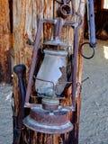 西部垂悬在木背景的农厂乡下老灯葡萄酒样式吊的样式生锈的古色古香的打破的油灯笼 图库摄影