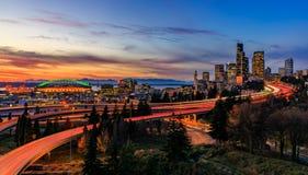 西雅图街市地平线全景在I-5 I-90高速公路互换之外的在与长的曝光交通足迹光的日落 库存照片