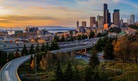 西雅图街市地平线和摩天大楼在I-5 I-90高速公路互换之外在日落在秋天与黄色叶子在 库存图片