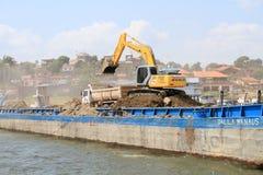 巴西,圣塔伦:倒空驳船的挖掘机 图库摄影