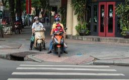 西贡,越南-与面罩的家庭在路面的滑行车骑马 图库摄影