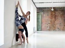 要做在一舒展的瑜伽锻炼的辅导员帮助在墙壁上 免版税库存照片