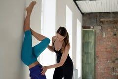 要做在一舒展的瑜伽锻炼的辅导员帮助在墙壁上 库存照片